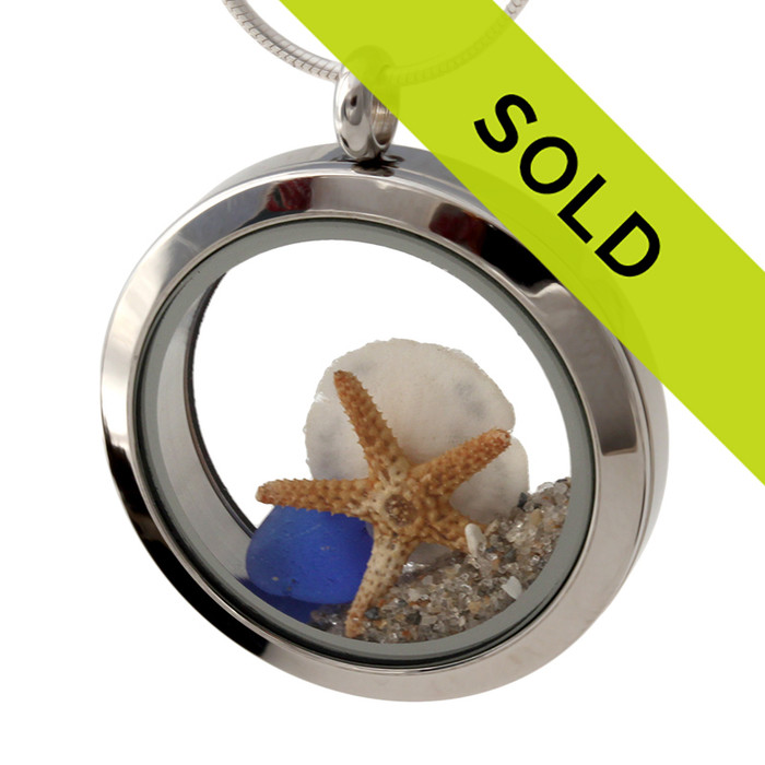 Simple small blue sea glass combined with a real sandollar and starfish in this beach on the go stainless steel locket necklace.
