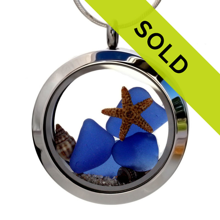 Blue sea glass pieces combined with a real starfish, tiny shells and beach sand in this sea glass locket necklace.