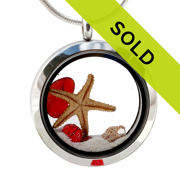 A Small piece of natural beach found ruby red sea glass combined with a real starfish, tiny shells and beach sand for your own personal beach on the go!