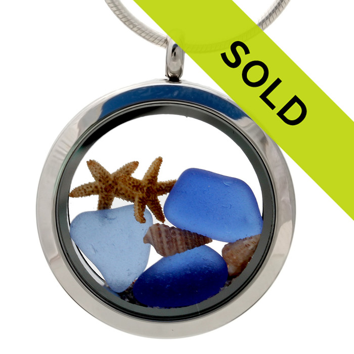 Blue sea glass pieces combined with a real starfish, tiny beach shells and beach sand in this sea glass locket necklace.