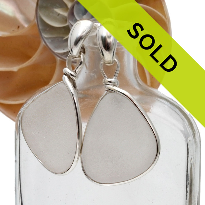 Perfect pieces of small white beach found sea glass set in a lovely pair of genuine sea glass earrings in sterling. Our Original Wire Bezel© lets all the beauty of the sea glass shine without altering the glass in any way! Presented on solid sterling silver cast posts with quality ear nuts.