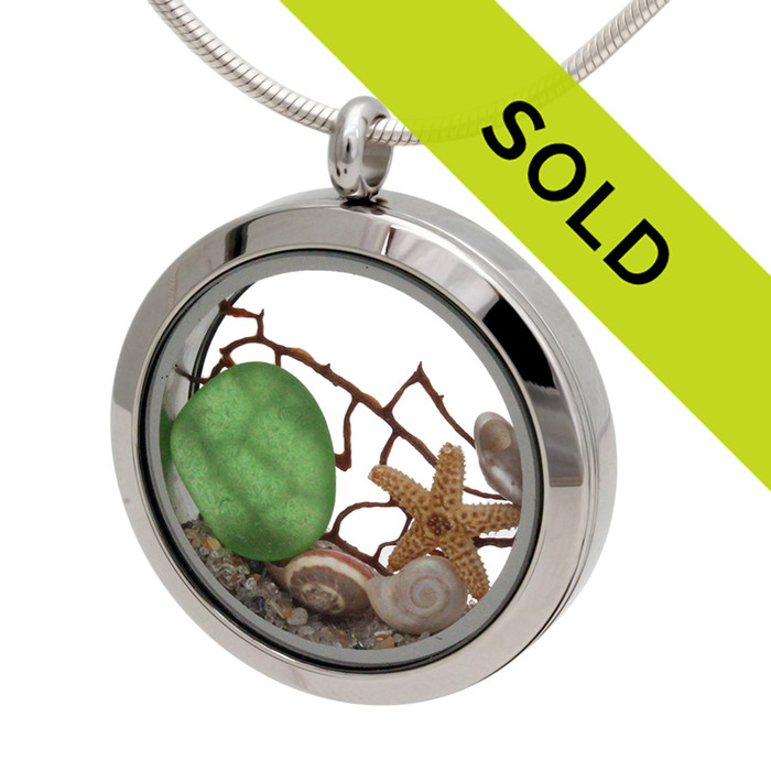 Green beach found sea glass piece combined with a real starfish, tiny nautilus shells and a piece of vintage sea fan. Real beach sand completes the beachy look in this sea glass locket necklace.