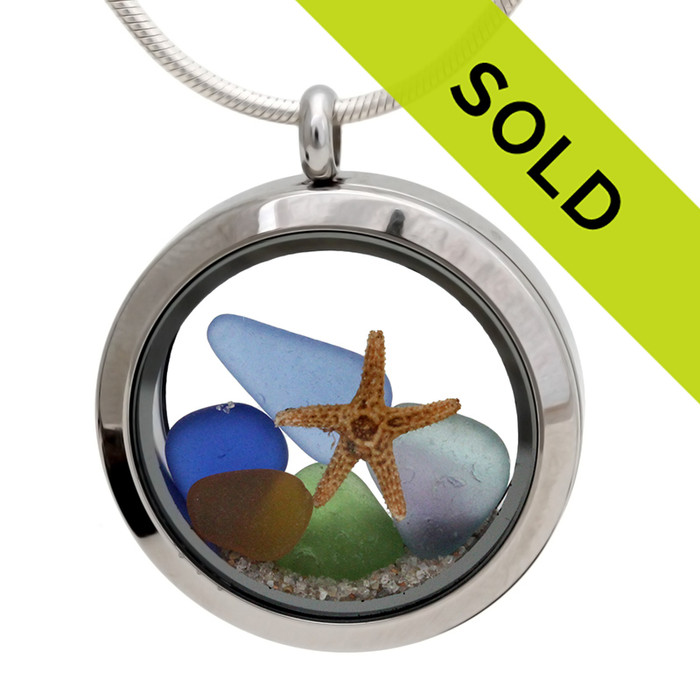 These jewels of the sea in blue, amber, green and one multi color sea glass piece are combined with a real baby starfish and beach sand. Sorry this locket has sold!