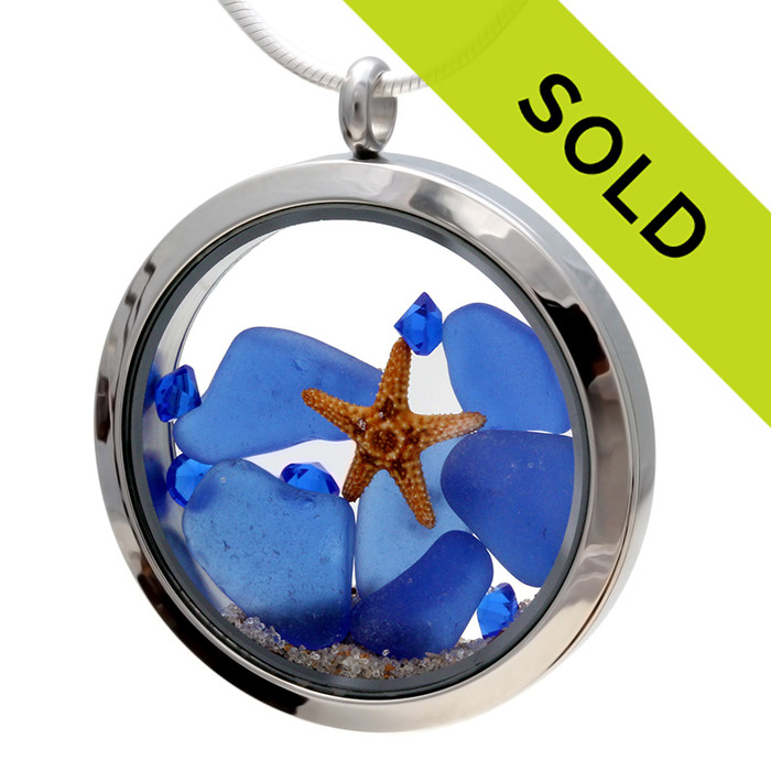 Genuine blue beach found sea glass pieces combined with a real starfish, shells, and sapphire color gems, and sand in this JUMBO 35MM stainless steel locket.