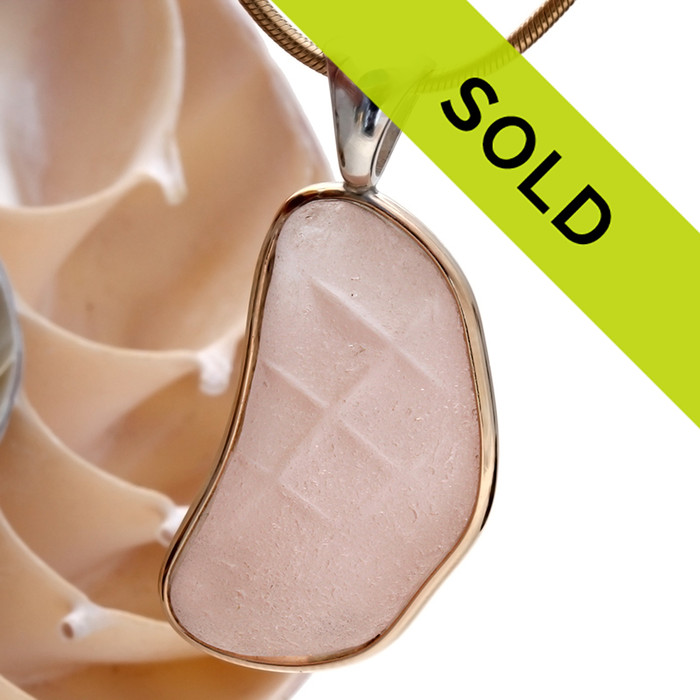 This AMAZING and HUGE peach sea glass still has shadows of its former like as a Depression Era Houseware.  It is set in a mixed metal gold and sterling silver Deluxe Wire Bezel setting. Very Versatile and elegant. CLASSIC! This setting leaves this amazing natural sea glass piece just the way it was found on  the beach! SORRY THIS ONE OF A KIND PIECE HAS SOLD!