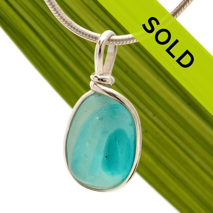 A beautiful larger piece of vivid blue green sea glass with a vivid amber center set for a necklace in our Original Sea Glass Bezel© in solid sterling silver setting.