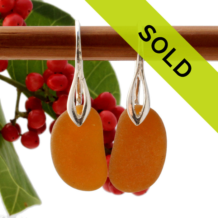 A pair of natural beach found sea glass earrings in a bright amber brown on sterling silver deco hooks