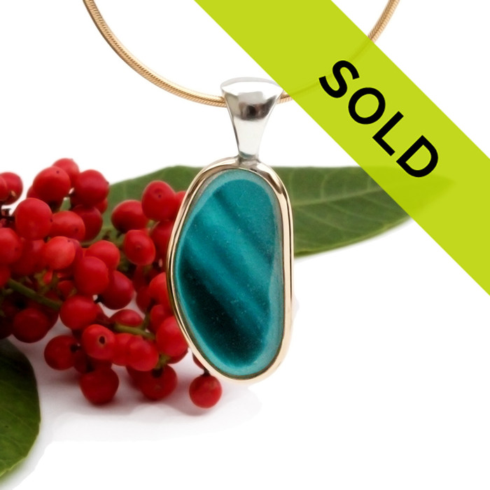 This sea glass is fused through with vivid teal color and set in a mixed metal gold and sterling silver Deluxe Wire Bezel setting. This setting leaves this amazing natural sea glass piece just the way it was found on the beach! Sorry this sea glass jewelry piece has been sold!