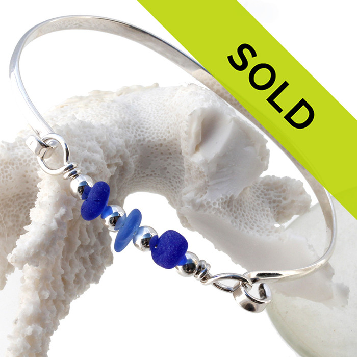 Three pieces of beach found sea glass in light and dark blue on this solid sterling silver half round sea glass bangle bracelet.