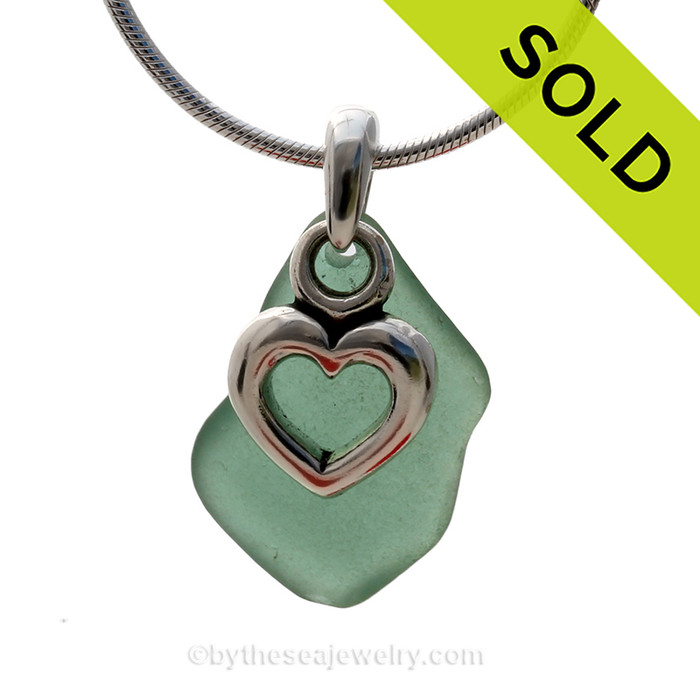 A perfect piece of natural green sea glass set on a solid sterling hand cast bail with a sterling silver heart charm. Sorry this sea glass necklace has been sold!