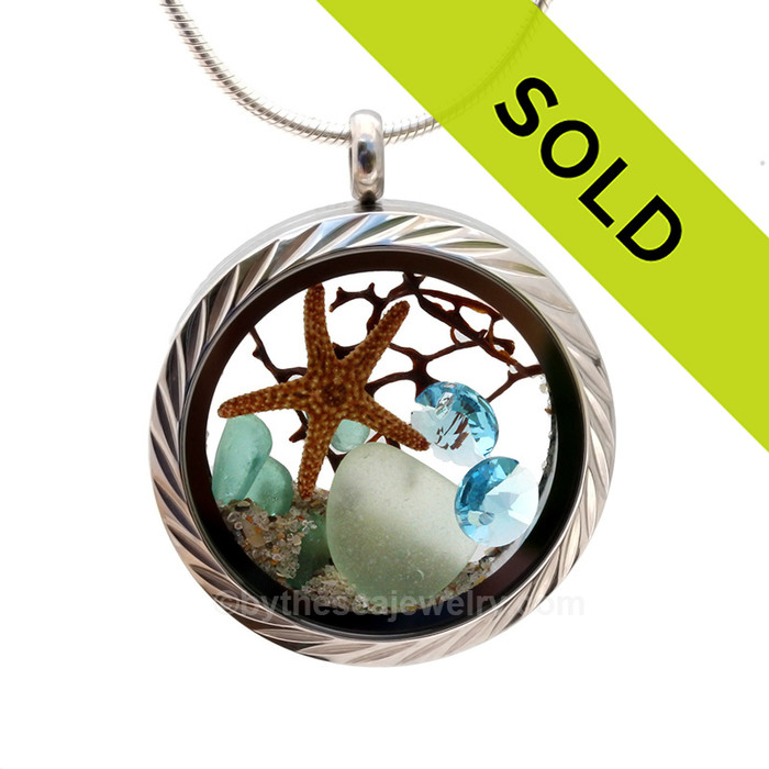 Genuine pastel sea glass pieces combined with a real starfish, a bit of vintage seafan and real beach sand in this stainless steel locket. Stunning aquamarine gems make this a great choice for anyone with a March Birthday. Sorry this sea glass jewelry piece has been sold!
