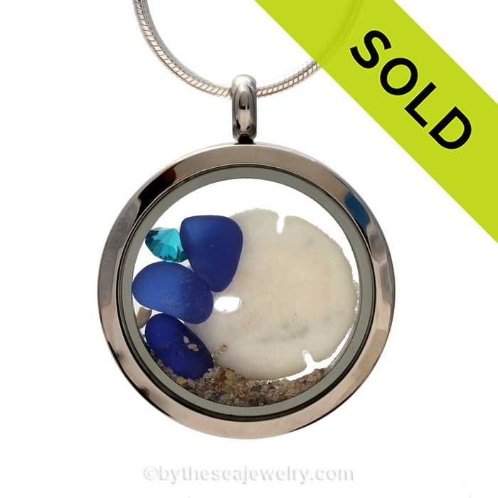 Beautiful pieces of natural Cobalt Blue sea glass combined in a stainless steel locket necklace with a real sandollar and finished with a Zircon crystal Gem. SOLD - Sorry This Sea Glass Jewelry Selection Is NO LONGER AVAILABLE!