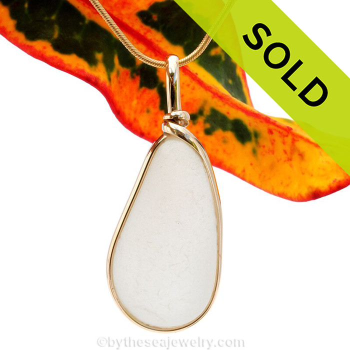 A large pure white natural sea glass piece set in our Original Wire Bezel setting in 14K Rolled Gold setting. Shown here on our 1MM snake chain which is available as an upgrade.