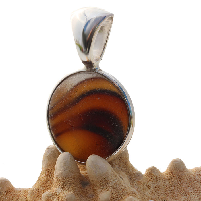 A True Sea Glass Pendant set in our Deluxe Wire Bezel© settings. A great piece mixed amber and clear that seems to come alive inside this amazing sea glass piece.