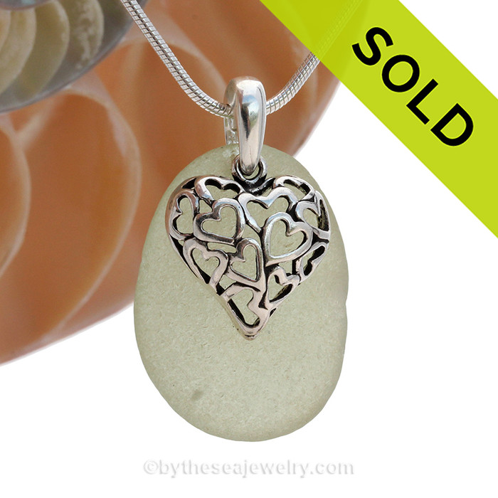 A  perfect piece of larger seafoam green  genuine sea glass with a solid sterling bail and detailed heart in hearts charm.