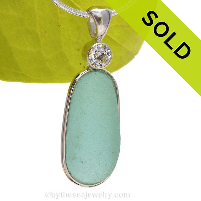 This is our Deluxe Wire design that leaves the glass UNALTERED from the way it was found on the beach. We bumped this up yet another level by incorporating a genuine SUPER PREMIUM Swarovski faceted cut 6MM brilliant CZ gemA Stunning Aqua Green Seaham Sea Glass Pendant set with a BRILLIANT CZ gem. SOLD - Sorry this Rare Sea Glass Pendant is NO LONGER AVAILABLE!