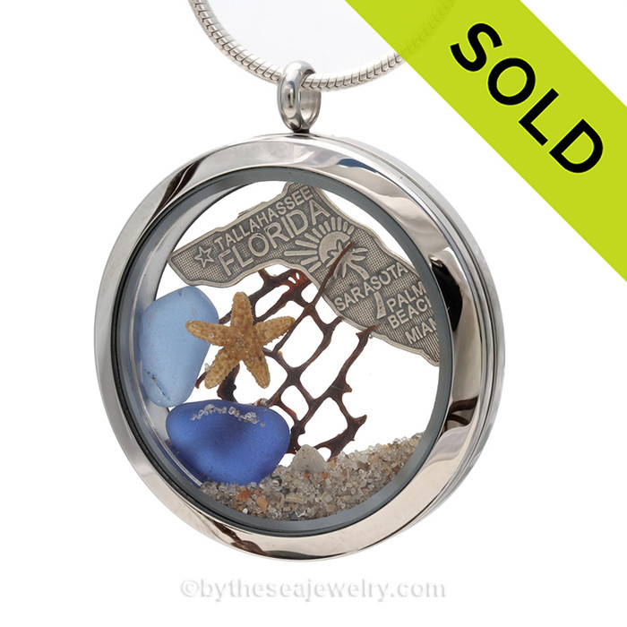 Beautiful pieces of blue Genuine sea glass pieces combined with a real starfish, seafan and a solid sterling Florida State Charm. Finished with real beach sand  in this JUMBO 35MM stainless steel locket necklace. SOLD - Sorry this Sea Glass Locket is NO LONGER AVAILABLE!