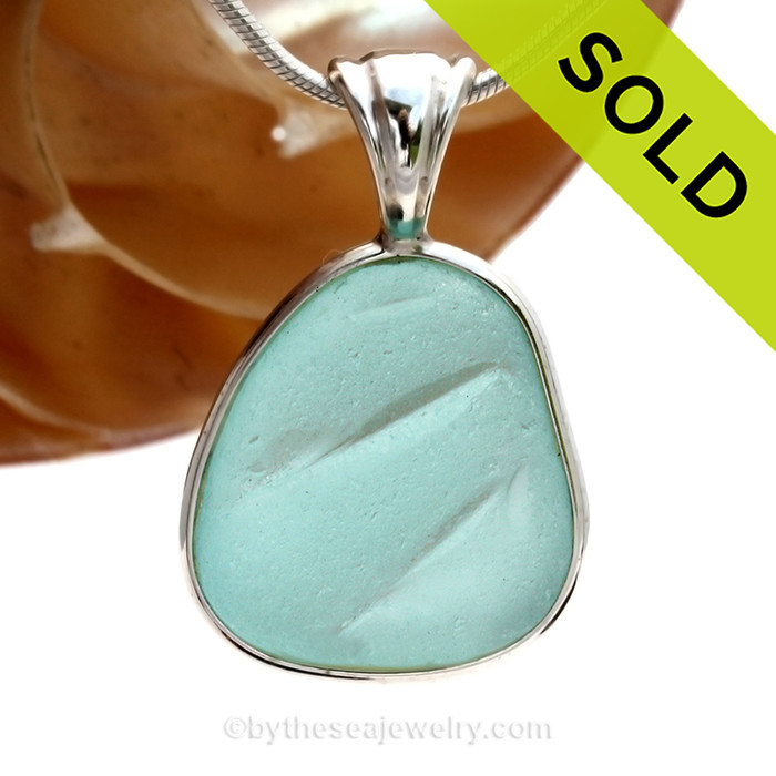 A wonderful shaped embossed piece of Aqua Blue sea glass in our In Our Deluxe Sterling Wire Bezel© necklace pendant. SOLD - Sorry this Rare Sea Glass Pendant is NO LONGER AVAILABLE!