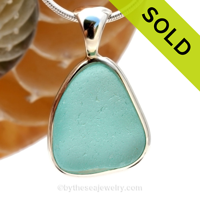 This is a beautiful smaller Aqua Blue Sea Glass set in our Original Wire Bezel© pendant setting in Sterling Silver .