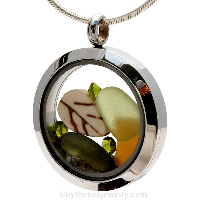 Genuine peridot green, bright amber and olive green  sea glass piece combined with a small carved leaf bead a real beach sand in this stainless steel locket. Finished with a  vivid peridot crystal gem for a bit of beachy bling.