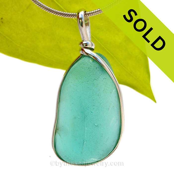 This is a beautiful Deep Vivid Aqua Green  Sea Glass set in our Original Wire Bezel© pendant setting in Sterling Silver .