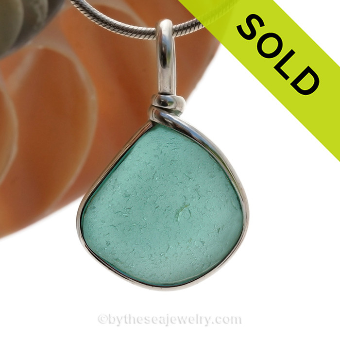 This is a beautiful and Thick and Vivid Aqua Green Genuine Sea Glass set in our Original Wire Bezel© pendant setting in Sterling Silver . This is our Original Wire Bezel© design that leaves the glass UNALTERED from the way it was found on the beach. Beautiful, Classic and Versatile. SOLD - Sorry this Rare Sea Glass Pendant is NO LONGER AVAILABLE!
