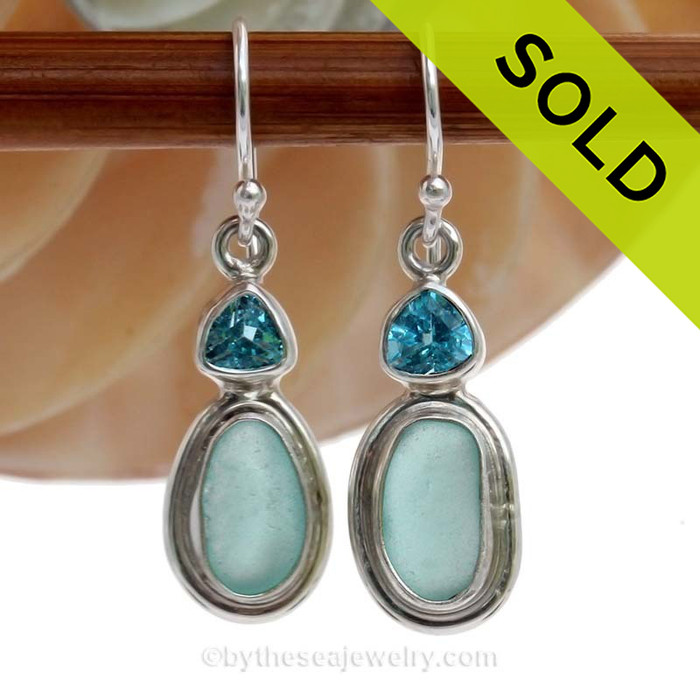 A stunning pair of tropical aqua sea glass earrings set in a finely crafted setting in sterling silver finished with a beach bling brilliant Blue Topaz round gem.