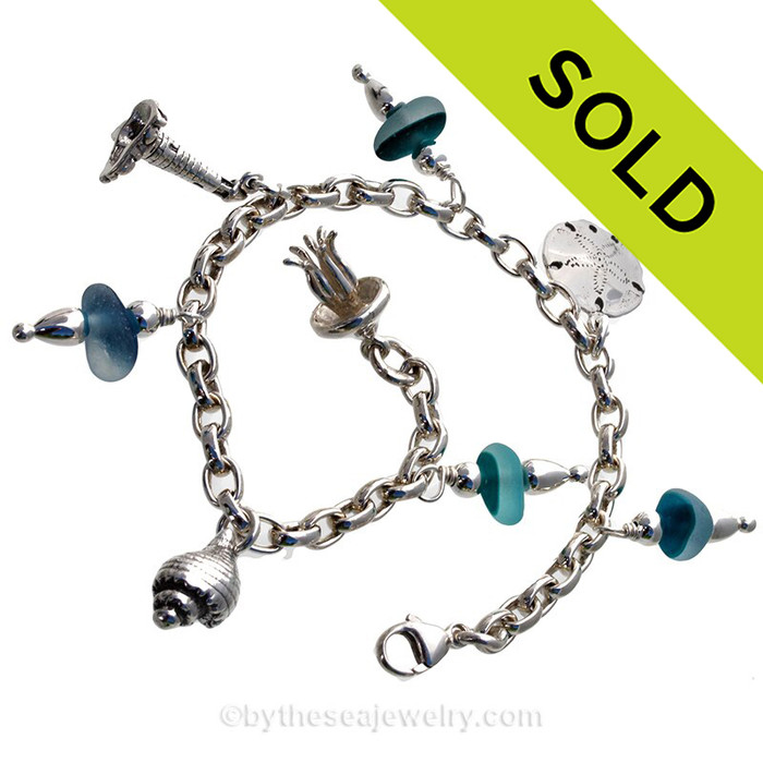 4 pieces of flashed RARE Vivid Aqua Blue Genuine beach found Sea Glass on a totally Solid Sterling Silver Charm Bracelet. The bracelet is made of top quality SOLID STERLING seamless Oval Rolo 5.3 MM links and has FULLY Soldered Utility Links for a lifetime of surety! The bracelet is secured with a and an oval Lobster Claw Clasp and finished with a detailed large Sterling Silver Jellyfish Charm. Other Solid Sterling charms include a Conch Shell, Lighthouse and Sandollar. SOLD - Sorry this Sea Glass Bracelet selection is NO LONGER AVAILABLE!