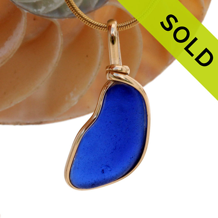 A rich and stunning neat shaped Cobalt Blue Sea Glass Pendant in my Original Gold Wire Bezel© This setting is open open on the front and back leaves the glass UNALTERED from the way it was found on the beach. Our Original secure setting allows you to reach up and feel the quality of this naturally age thick sea glass!
