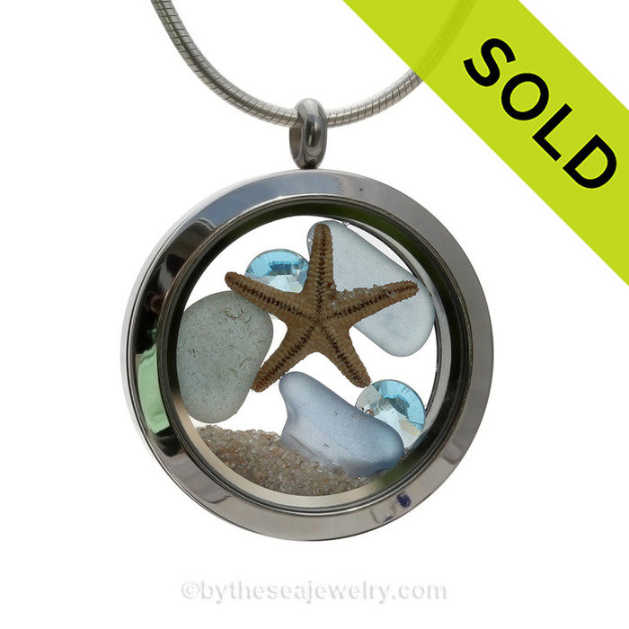 Carolina Blue Sea Glass in a crystal and stainless steel locket combined with a baby starfish and vivid a Aquamarine Crystal Gems. Finished with real beach sand for your personal beach on the go! SOLD - Sorry this Sea Glass Locket is NO LONGER AVAILABLE!!!