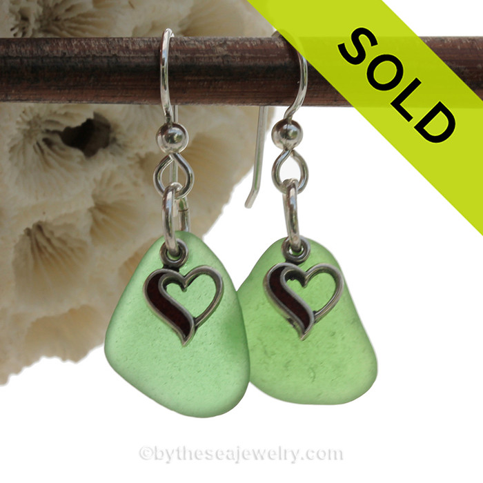 A simple pair of genuine green sea glass earrings with sterling heart charms in a lightweight simple setting.