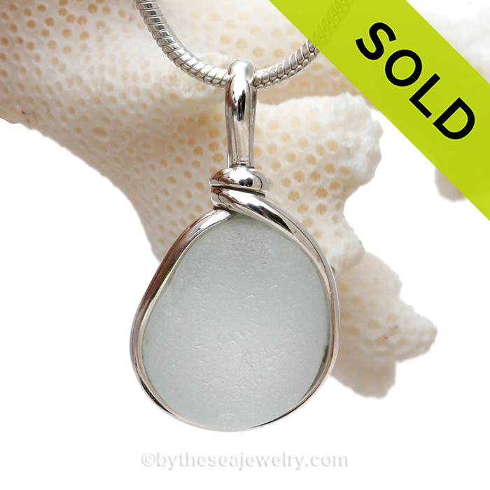 A perfect teardrop shaped super pure white piece of sea glass set in our Original Wire Bezel© necklace pendant setting.  This glass hails from a beach in England and is the result of a late 19th century glass industry in the Tyne & Wear region. Scrap glass and discards where washed out to the North Sea and now wash up on a local beac