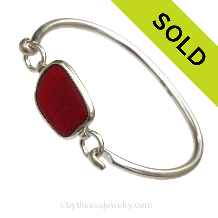 A PERFECT piece of deep Vivid Ruby Red Sea Glass Bangle Bracelet set in our Deluxe Wire Bezel© Sterling Silver Setting. This setting leaves the sea glass piece TOTALLY UNALTERED from the way it was found on the beach.