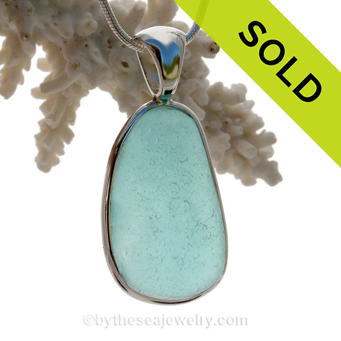 This is a beautiful VIVID and LARGE Aqua Blue Genuine Sea Glass set in our Deluxe Wire Bezel© pendant setting in Solid Sterling Silver .