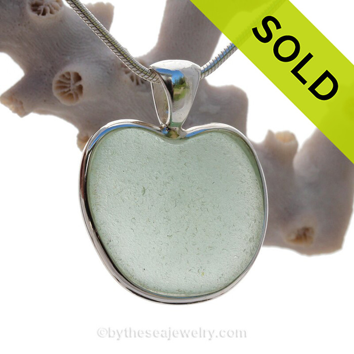 A beautiful  large Seafoam Green TOTALLY NATURAL Sea Glass Heart Pendant set in our Deluxe Wire Bezel© setting in Sterling. This piece features the glass and beauty of the collected seafoam sea glass and is presented on a professionally our Deluxe Wire Bezel Setting© that leaves the sea glass UNALTERED from the way it was found on the beach.