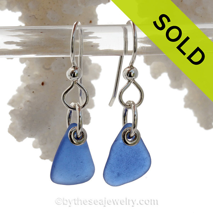 A pair of natural surf tumble sea glass earrings in a lucky cobalt blue on sterling fish hooks.