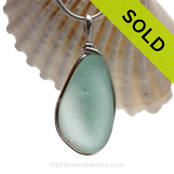 A Thick Aqua Blue beach found glass from is set in our Original Wire Bezel© pendant setting in sterling silver.