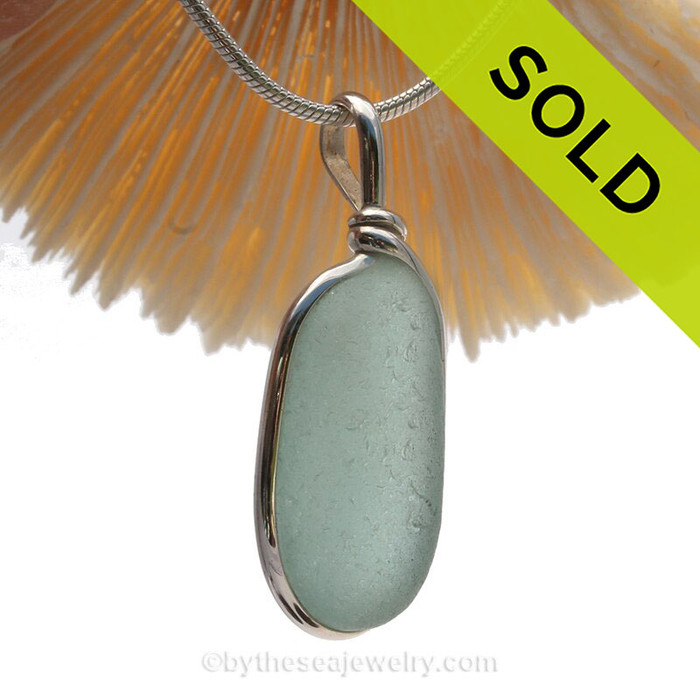 A PERFECT Oval of Aqua Blue beach found glass from is set in our Original Wire Bezel© pendant setting in sterling silver