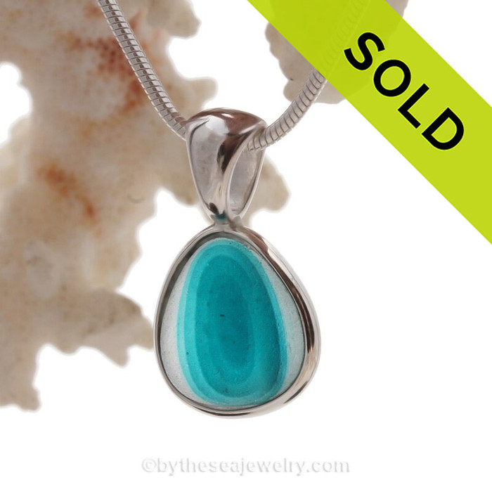 An stunning combination of vivid mixed electric aqua and white in this very old English Sea Glass piece and set in our Deluxe Wire Bezel© necklace pendant setting in sterling silver.