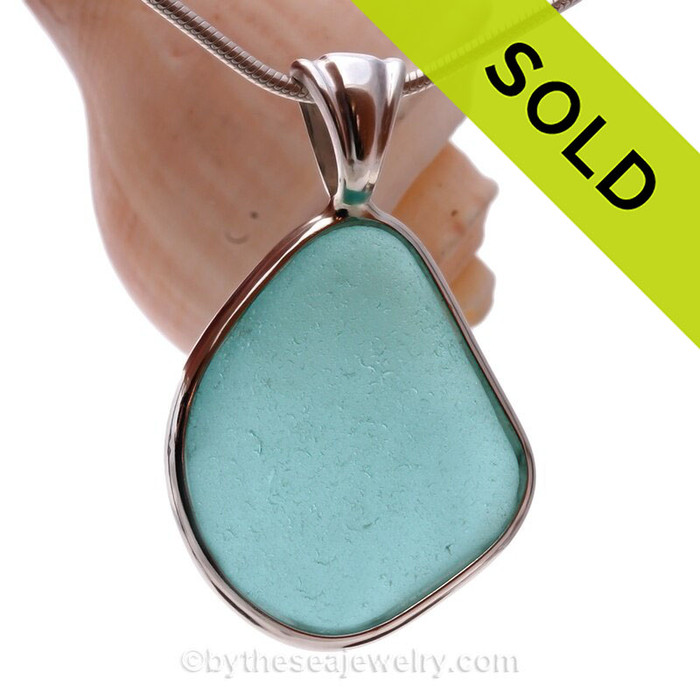 This LARGE and flat triangle of rich Aqua Blue Genuine Sea Glass set in our Deluxe  Wire Bezel© pendant setting .
