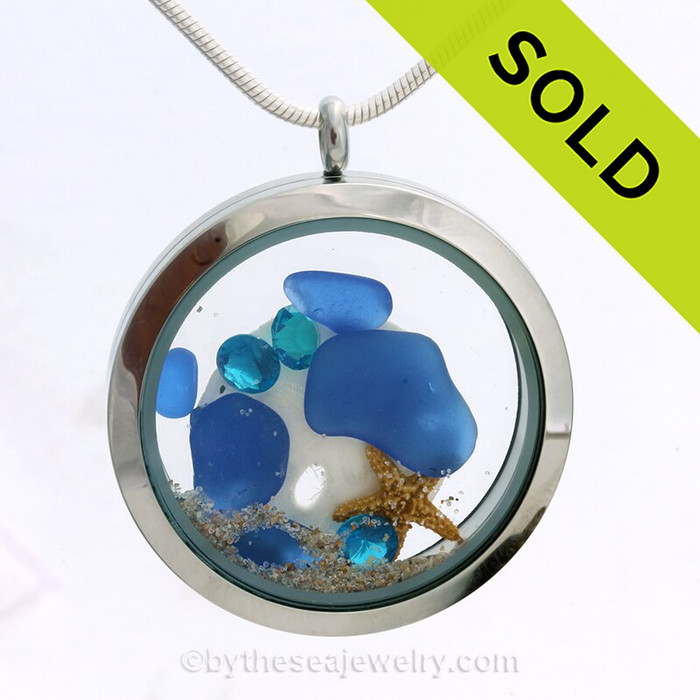 Genuine blue beach found sea glass pieces combined with a real starfish, baby sandollar, and sapphire color gems, and sand in this JUMBO 35MM stainless steel locket. SOLD - Sorry this Sea Glass Jewelry selection is NO LONGER AVAILABLE!