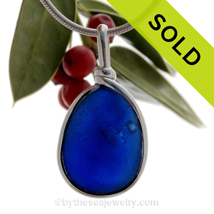 A bumpy bubbly piece of Cobalt Blue Genuine Sea Glass  bottle bottom with in our signature Original Wire Bezel© pendant setting in Sterling Silver.