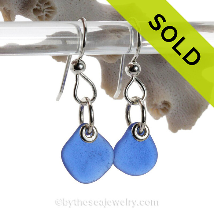 A pair of natural surf tumbled blue sea glass earrings in a lucky cobalt blue on sterling fish hooks. Finished with Solid Sterling Details.