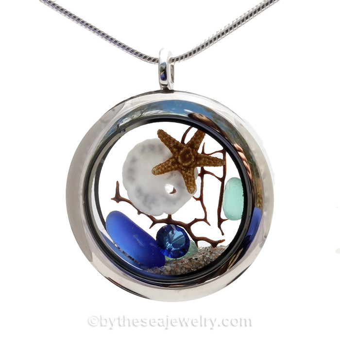 Beautiful blue and Aqua sea glass combined in a stainless steel locket necklace a real starfish, baby sandollar and beach sand. A  great choice for any ocean lover! Finished with a sapphire blue crystal gem.