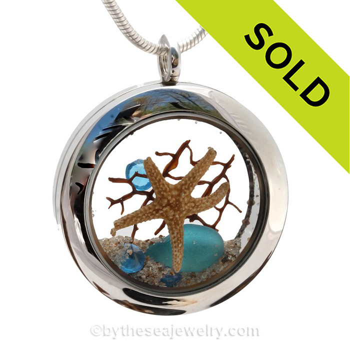 A STUNNING piece of electric aqua sea glass with a real starfish, seafan bit and crystal gems.