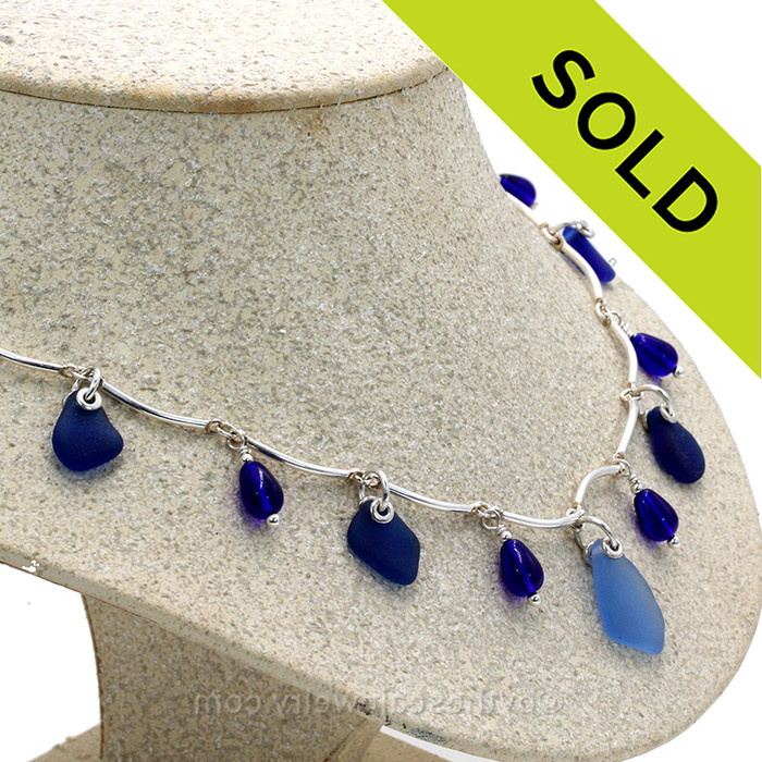 7 pieces of Blue Genuine Beach Collected Sea Glass on a Solid Sterling Silver Curved Bar Necklace with Sterling Beautiful Sterling Teardrop Beads in a elegant necklace.