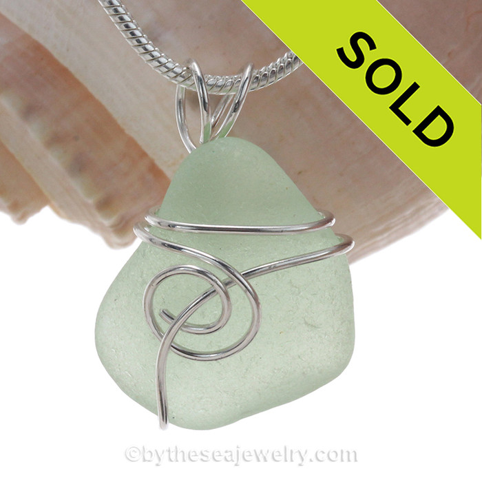 A small perfect piece of seafoam green sea glass is set in our popular Sea Swirl setting in sterling silver.