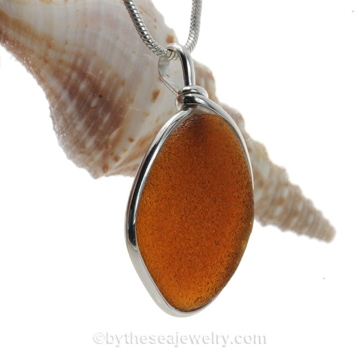 Perfect amber brown natural sea glass piece set in our Original Wire Bezel setting in sterling silver. Shown here on our 2MM snake chain which is available as an upgrade.