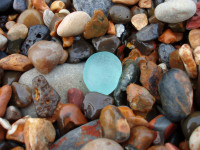 aqua sea glass in pebbles on beach