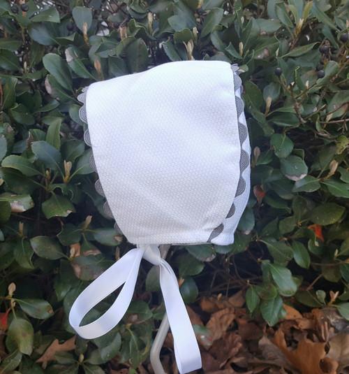 White pique bonnet with grey trim.